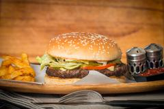 Cheeseburger served  with French Fries and Beer - stock photo