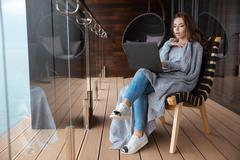 Amazed woman sitting wrapped in knitted coverlet using laptop Stock Photos