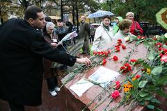 Politician Vladimir Milov lays flowers at a rally memory of Anna Politkovskaya - stock photo