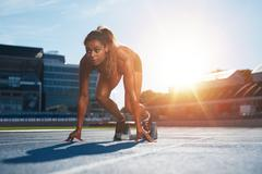 Woman about to start a sprint - stock photo