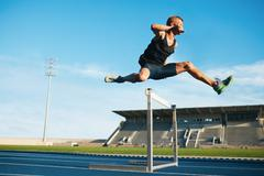 Professional sprinter jumping over a hurdle Stock Photos