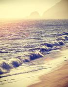 Vintage filtered beach at sunset with flare effect, California. - stock photo