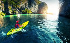 Kayaking near rocks - stock photo