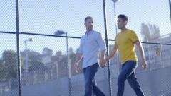 Gay Couple Hold Hands And Walk Through Park, Past Tennis Courts - stock footage