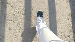 Feet in sports shoes walking on asphalt at bridge Stock Footage