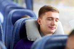 Stock Photo of happy young man sleeping in travel bus with pillow