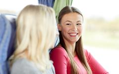 Stock Photo of happy young women sitting in travel bus
