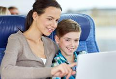 Stock Photo of happy family with tablet pc sitting in travel bus