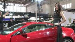 Model posing with Aston Martin car, Beijing Stock Footage