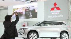 Chinese man films Mitsubishi car, Auto Show Stock Footage