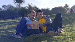 Gay Couple Hang Out In Park And Use A Tablet Togethe Stock Footage