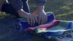 Asian Man Rolls Up His Picnic Blanket At Park, Talks To Someone Off-Screen Stock Footage