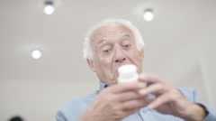4K Cheerful elderly gentleman in a wheelchair looking at his medication - stock footage