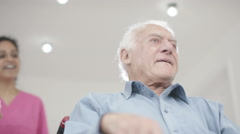 4K Caring home support nurse taking care of elderly man in wheelchair - stock footage