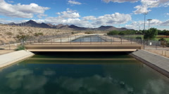 Aerial  over canal bridge with mountain background Stock Footage