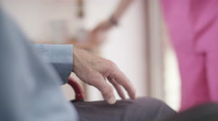 4K Caring home support nurse holding the hand of elderly man in wheelchair - stock footage