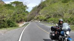 Biker riding mountain road Stock Footage