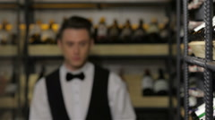 Cheerful young sommelier holding a wine bottle - stock footage
