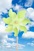 Colorful green pinwheel over blue sky with clouds Stock Photos