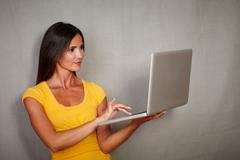 Good-looking female using laptop while standing against grey texture backgrou Stock Photos