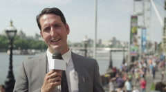 Stock Video Footage of 4K TV reporter doing live piece to camera outdoors in the city of London
