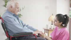 4K Caring home support nurse comforting sad elderly man in a wheelchair Arkistovideo