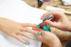 Nails painting woman with brush in Nail Salon - stock photo