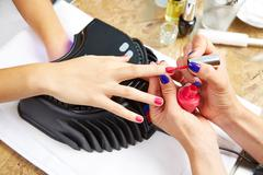 Nails painting with UV dry lamp in blue light - stock photo
