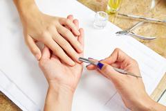 Cuticle pusher tool in nails salon woman hands - stock photo