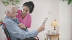 4K Caring home support nurse helping elderly man to use a computer Stock Footage