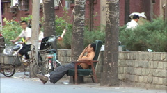 Chinese man napping on street, Beijing - stock footage