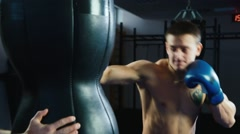 Athletic man boxing. Strong hits the punching bag Stock Footage