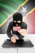 Hacker with ID card in hand and flag on background - Saint Kitts and Nevis Stock Photos