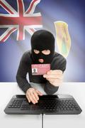 Hacker with ID card in hand and flag on background - Turks and Caicos Islands - stock photo