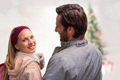 Composite image of smiling man having arm around girlfriend looking at camera - stock photo