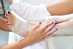 Aplying nourishing moisturizer mask woman legs - stock photo