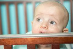 Adorable baby in his crib - stock photo