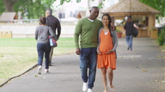 4K Happy mixed ethnicity couple expecting a baby going for a walk in the park - stock footage