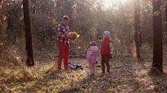 The family has fun in autumn park and throw leaves up Stock Footage