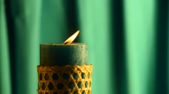 Teal candle trembling flame with green curtain background and blown out Stock Footage