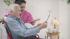 4K Caring home support nurse helping elderly man to use a computer - stock footage