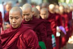 Burmese monks queueing for meal - stock photo