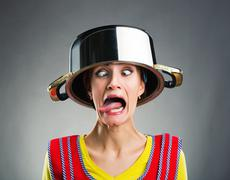 Crazy housewife with sause pan on her head - stock photo