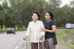 Senior woman using a walker cross street Stock Photos
