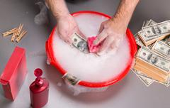 Hands are washing dollars in foam - stock photo