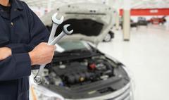 Hand of car mechanic in auto repair service. - stock photo