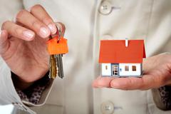 Woman Hands with little house and key. Stock Photos