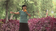 Chinese woman sings traditional song in park Stock Footage