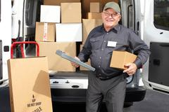 Stock Photo of Senior delivery man with parcel near truck.