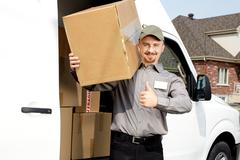 Postman with parcel near delivery truck. - stock photo